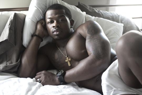 black hunk in bed wearing cross