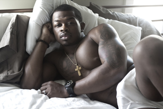 black hunk in bed wearing cross